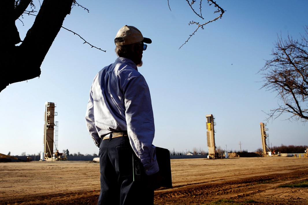 An almond farmer watches oil wells that have sprouted near almond orchards in Shafter.