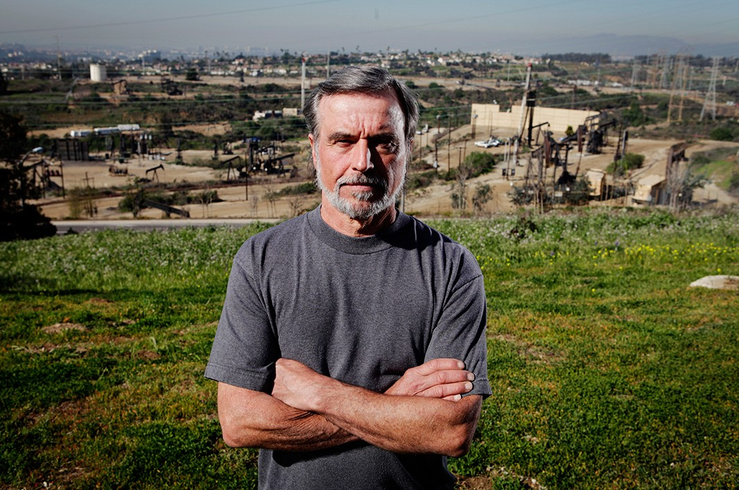 Gary Gless, president of the non-profit, grassroots group Citizens Coalition for a Safe Community, stands on a hill in his neighborhood overlooking the Inglewood Oil Field.