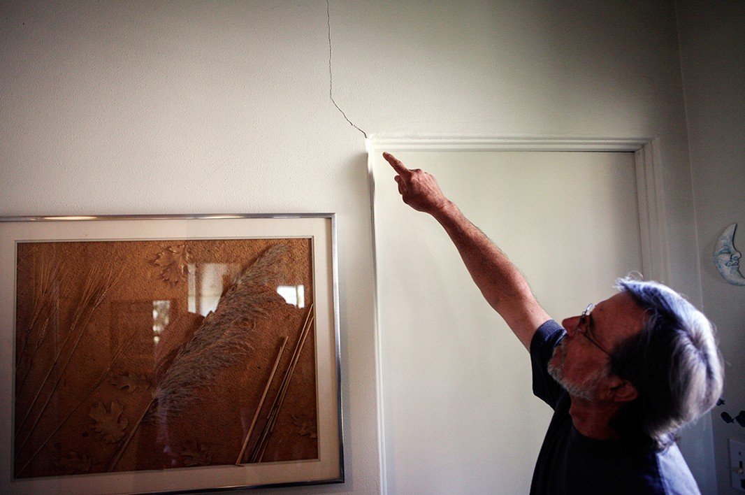 Gless points to a new crack in the wall of his Windsor Hills home, which are appearing nearly daily due to the increase in activity at the Inglewood Oil Field near his Los Angeles area home.
