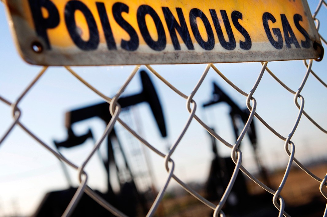 A sign hangs by an oil field in California, warning of hazardous fumes.