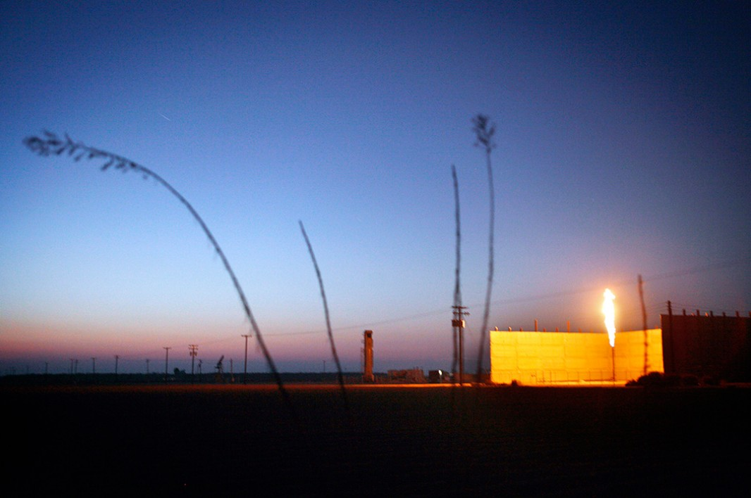 As the sun sets on another California day, a flare burns in an oil field in Shafter, CA.