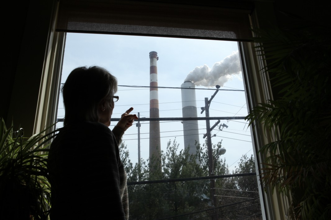A woman looks out of her window at a coal-fired power plant. (Chris Jordan-Bloch / Earthjustice)