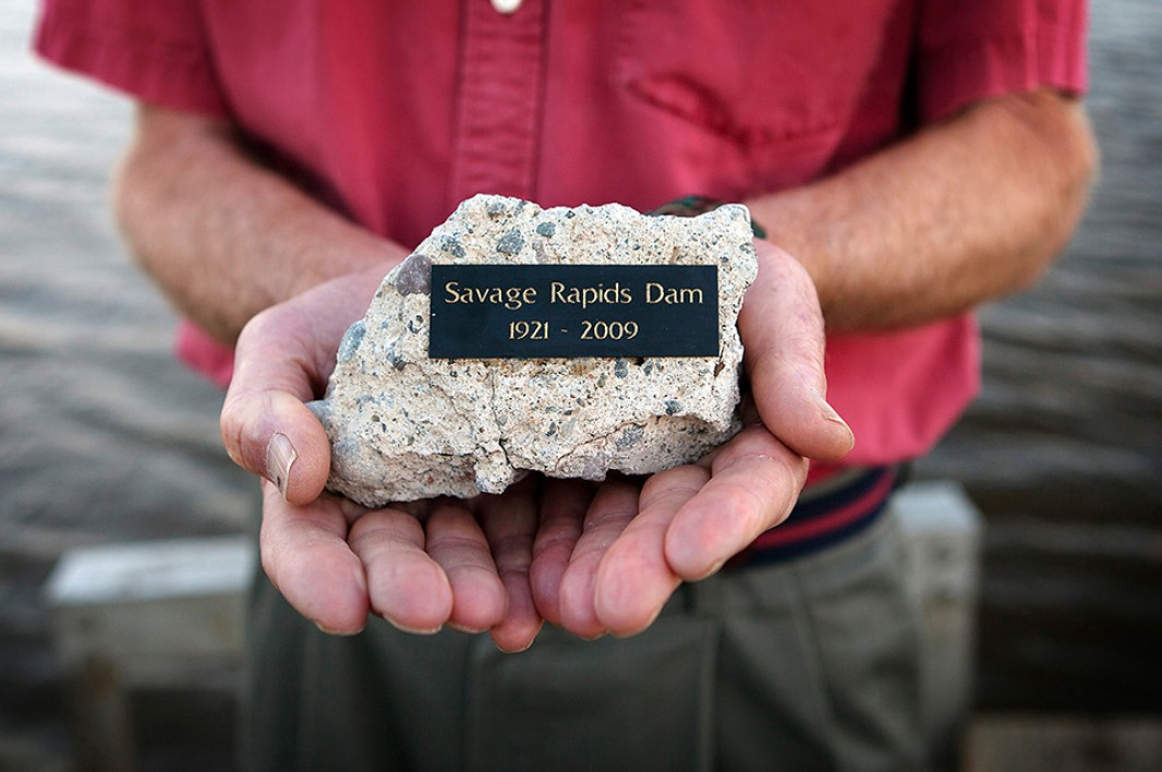 """Attorney Mike Sherwood holds a piece of the Savage Rapids dam given to him after his litigation played a key role in the removal of the dam, known as the """"worst salmon-killing dam on Rogue River."""""""