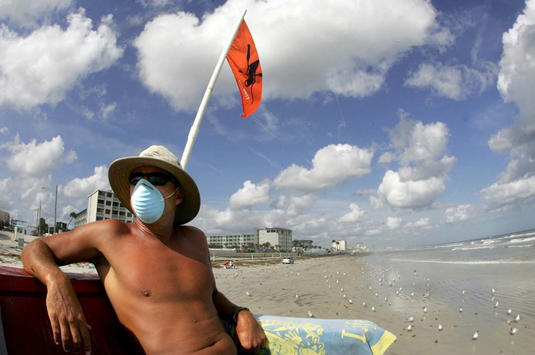 A lifeguard sits near a red tide warning notice at a Volusia County beach during red tide event in October of 2007.