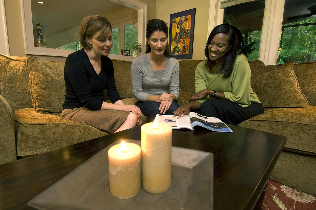 Three women sit on a couch next to a burning candle. (U.S. Fire Administration / FEMA)