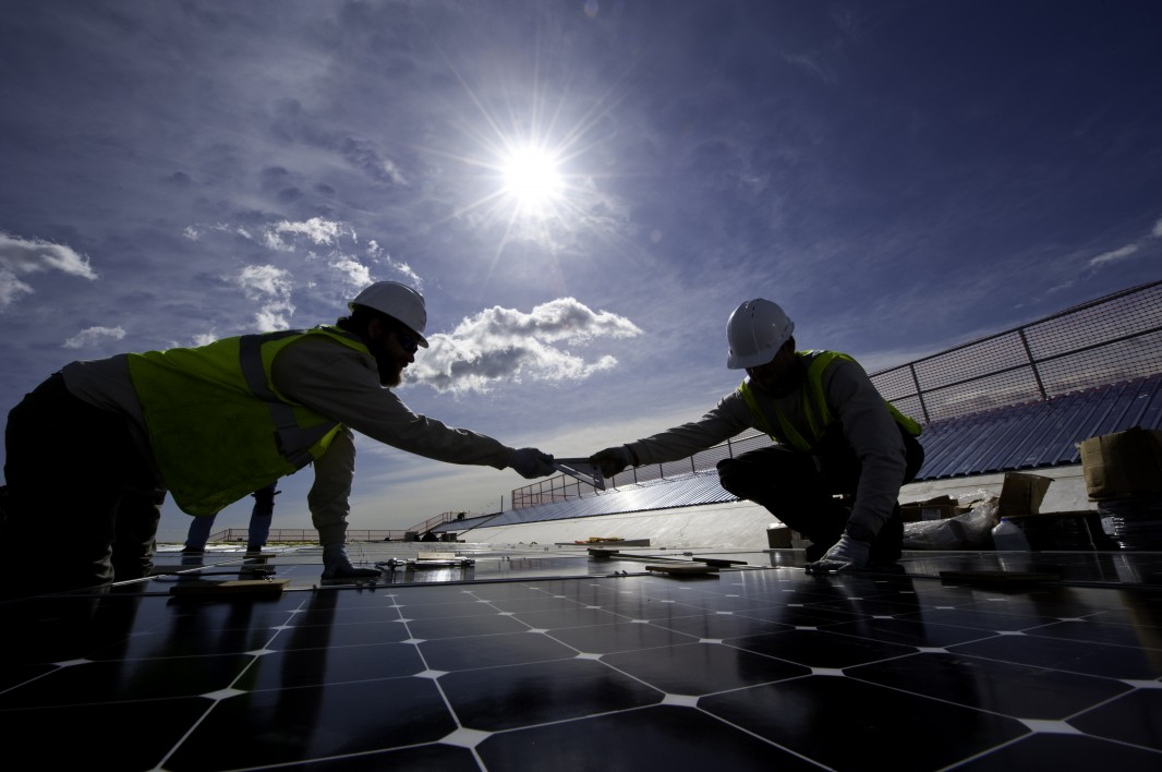 Two workers install a solar panel on a roof in Colorado. (Dennis Schroeder / NREL)