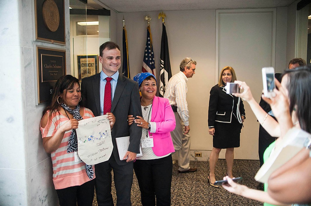 Back in the Hart Senate Office Building, New York constituents Lidia Franco (left) and Alina Diaz take a photo with a senator's aide.