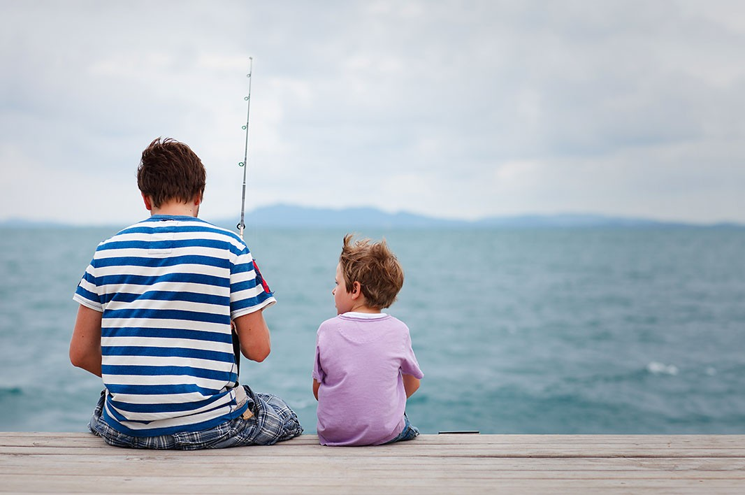 A father and son go fishing off a pier. (BlueOrange Studio / Shutterstock)