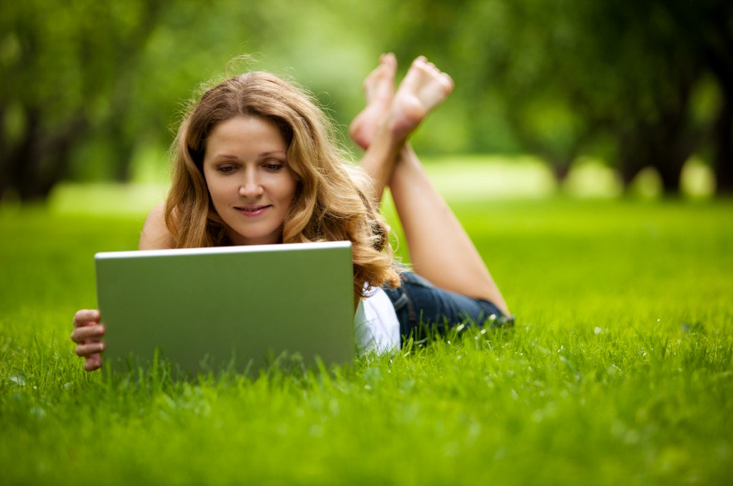 A woman uses her laptop on the grass. (Max Bolotnikov / iStock)