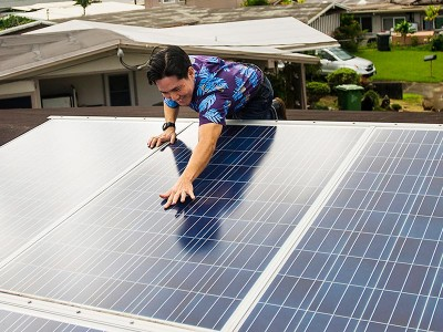 Attorney Isaac Moriwake examines solar panels installed on his rooftop. (Matt Mallams / Earthjustice)