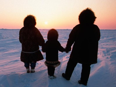 Family framed against the sunset, in the Arctic. (Jeff Schultz / National Geographic Creative)
