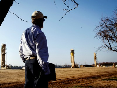 A farmer watches oil wells that have sprouted near almond orchards in Shafter, Kern County, California.