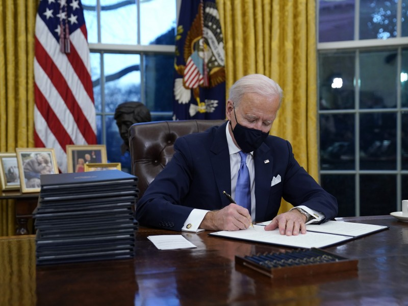 Joe Biden signs his first executive orders in the Oval Office on day one of his administration, January 20, 2021.