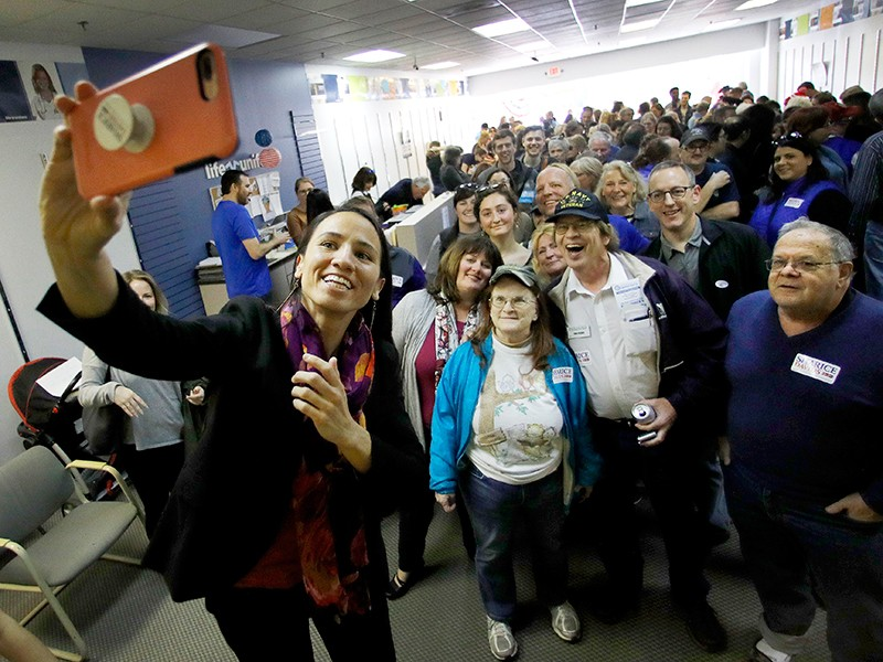 Democratic house candidate Sharice Davids takes a photo with supporters during a rally at her campaign office on Nov. 3, 2018, in Overland Park, Kan. Davids challenged Incumbent Republican U.S. Rep. Kevin Yoder for Kansas' 3rd Congressional District seat,
