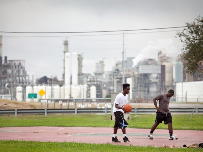 Teenagers play basketball in the Carver Terrace housing project in 2013 in Port Arthur, Tex.