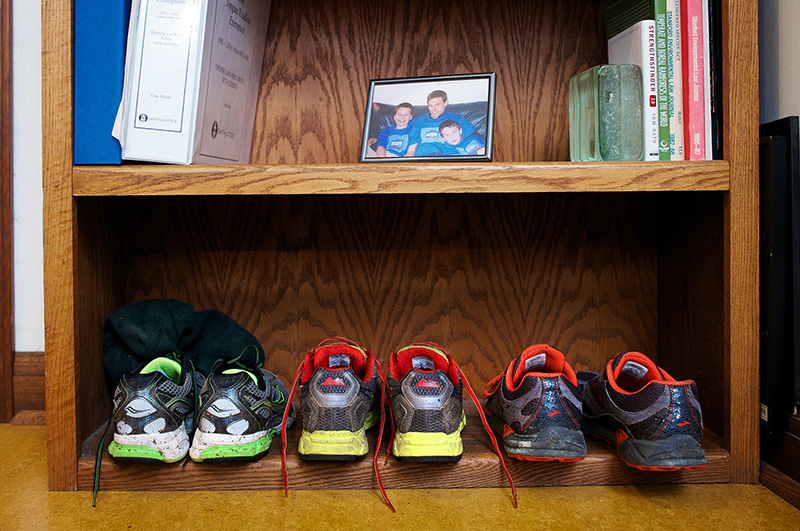 A shelf in Waldo's Earthjustice office holds his shoes and an older photo of him with his two sons. Biking shoes are in the middle, flanked by running and around-town shoes.